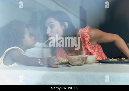 Madre e hija comer pasta en la mesa de comedor compartiendo un espagueti