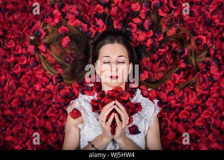Directamente encima de foto de mujer acostada sobre Pétalos de Rosas