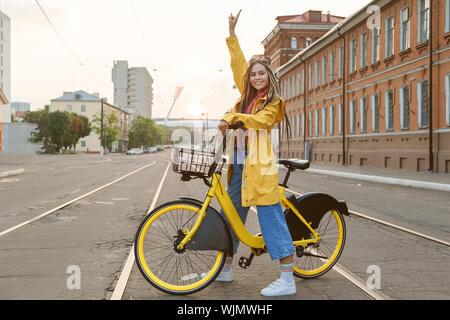 Mujer joven vistiendo abrigo color amarillo y pigtails, montando en bicicleta en la ciudad.