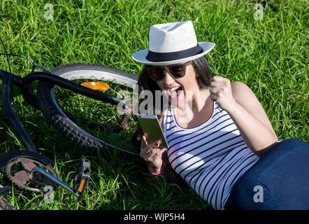 Jóvenes Emocionados mujer utilizando el dispositivo mientras está acostada en la hierba cerca de bicicleta. Lanzarote, la isla de Gran Canaria, España.