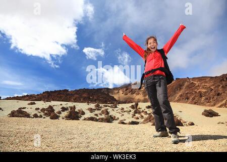 Senderismo feliz con los brazos en el aire. Mujer caminante emocionado y alegre, viajando en el Teide, Tenerife, Islas Canarias.