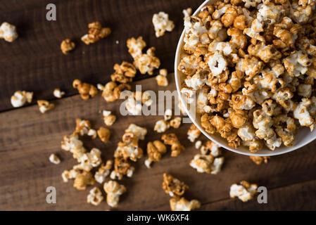 Directamente encima de tiro de Popcorns en recipiente sobre mesa de madera