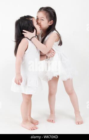 Las niñas retrato. Besos hermana asiática gemelos sobre fondo liso.