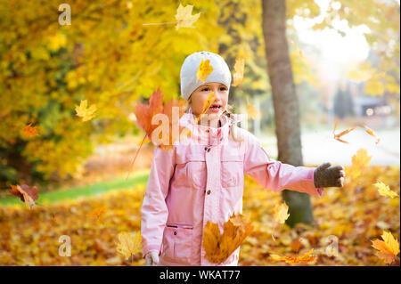Cute Little Girl con dientes perdidos jugando con el amarillo de las hojas caídas en otoño bosque, trowing en el aire. Niño feliz riendo y sonriendo. Sunny