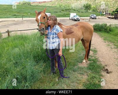 Vista lateral de la mujer madura besar a caballo marrón en el campo Foto de stock
