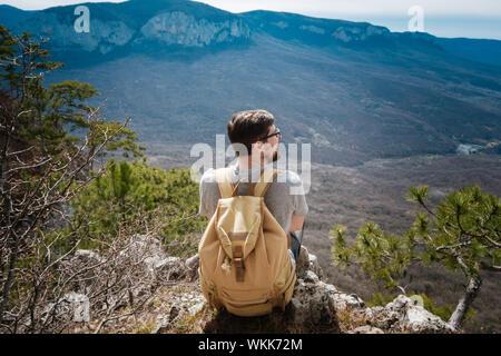 Young hipster hombre en el Spring Mountains. Hipster con una mochila a la espalda se va de viaje