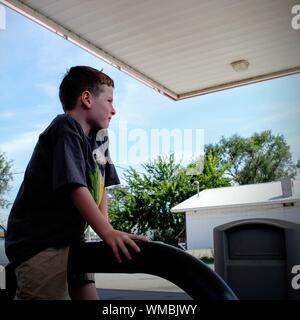 Vista lateral de una cuidadosa muchacho sentado en la Gasolinera contra Sky
