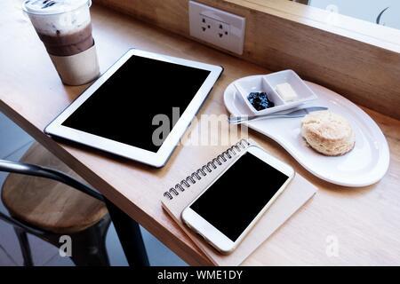 Teléfono inteligente con un café en la mesa del café