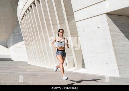 De cuerpo completo atleta femenina en ropa deportiva corriendo sobre hormigón