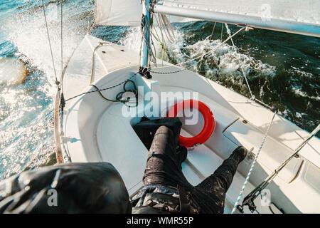Olas pulverizando sobre la cubierta de un pequeño yawl durante un viaje de viento sobre el océano