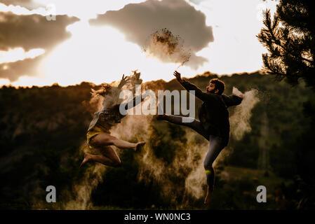Hombre hermoso con una hermosa muchacha bailando mientras salta sobre la montaña Foto de stock