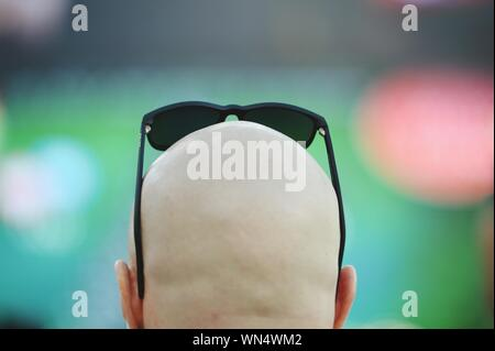 Vista trasera del hombre con la cabeza rapada con gafas de sol