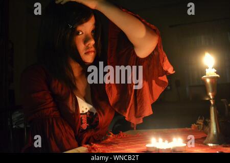 Retrato de mujer con vela encendida en el cuarto oscuro Foto de stock