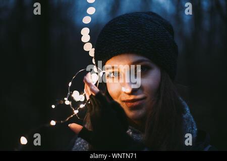 Close Up retrato de joven bella celebración luces de Navidad