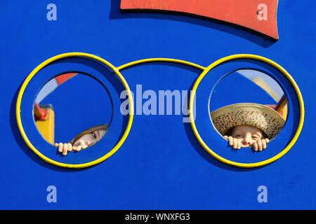 Niño y niña mirando a través del agujero en la pared de Playhouse. Dos niños escondidos detrás de la pared Playhouse y peeking o peeping.