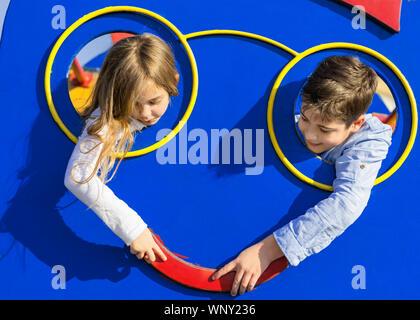 Chico y chica de tocar con la mano. Los niños ponga la cabeza a través del agujero en el patio de recreo. Pareja joven que a los niños les encanta. Concepto de amor y amistad.