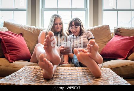 Dos chicas adolescentes sentados en el sofá con los pies para arriba mirando a celular.