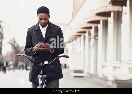 El hombre en traje de texto en el teléfono, de pie, con la bicicleta en la calle