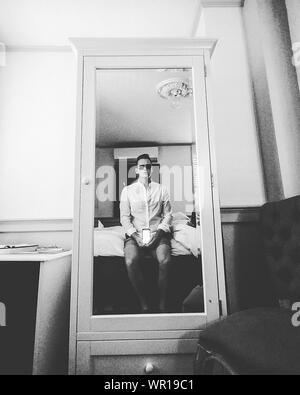 Hombre teniendo Selfie mediante Smart Phone reflejando en el espejo Foto de stock