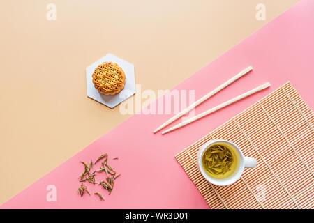Plano de laicos Festival Chino, mediados de otoño Festival de postre torta de luna sobre fondo de colores con té verde y palillos. Vista superior, copia el espacio, Boceto