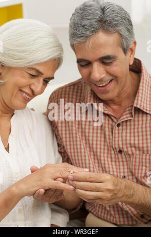 Hombre mayor poniendo el anillo en el dedo de su esposa
