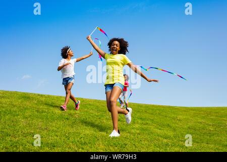 Feliz niñas ejecutar con cintas en el campo