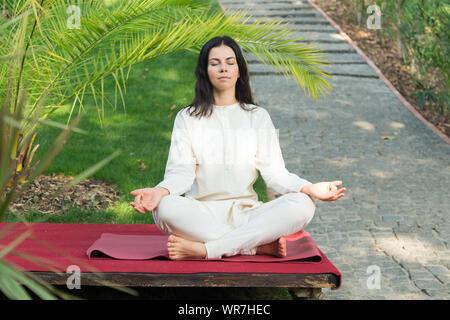 Mujer morena medita sobre la naturaleza de fondo. Ejercicios de yoga en el retiro.