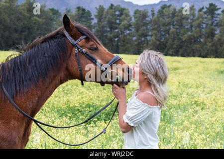 Mujer besar su castaña de caballo árabe en su nariz, de pie uno frente al otro, al aire libre, con campo de flores amarillas. Foto de stock
