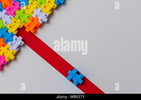 Puzzle de plástico de colores sobre papel blanco de fondo, falta un rompecabezas en línea roja para completar con copia espacio, estrategia empresarial trabajo en equipo