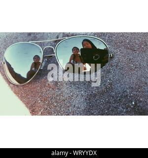 Amigas teniendo Selfie reflexionando sobre gafas de sol en la playa Foto de stock