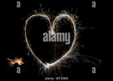 Forma de corazón iluminado de fuegos artificiales por la noche
