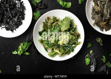 Secar las algas, las verduras del mar, cerca de la Fotografía cenital sobre un fondo negro