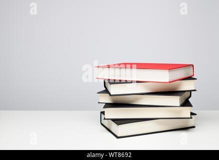 Pila de cuatro negros y uno rojo en una mesa de libros de tapa dura Foto de stock