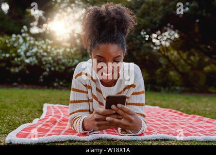Relajado sonriente joven afroamericana acostado sobre una manta sobre el césped en el parque a través de teléfono móvil - Estudiante en su móvil en College Park