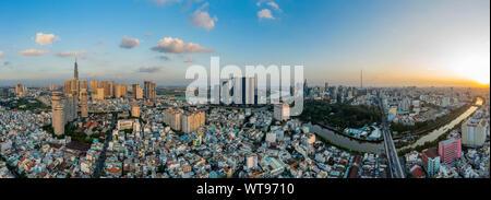 Ultra alta resolución antena dramático panorama de Binh Thanh district Ho Chi Minh tomando en los principales edificios de la ciudad y enfrente del río al atardecer