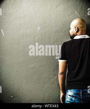 Vista trasera del hombre con la cabeza rapada contra la pared