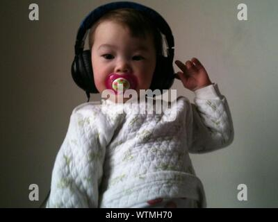 Lindo bebé niña escuchando música desde auriculares contra la pared