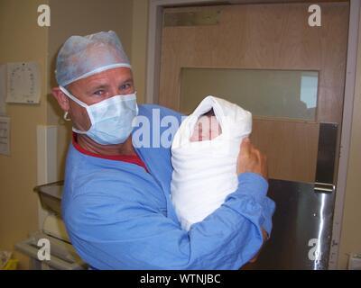 Retrato del Doctor llevando bebé recién nacido en el Hospital