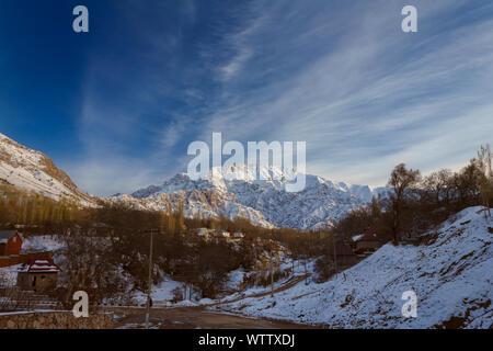 Alpes montaña parcialmente cubierto por la nieve por encima de las pequeñas aldeas, finales de otoño