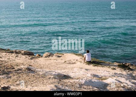 Turista solitario hombre caminante está sentada sola en una costa rocosa y disfrutando de la puesta de sol. Vistas al océano libre.