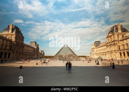 Vista del Museo del Louvre y la pirámide de cristal con los turistas.