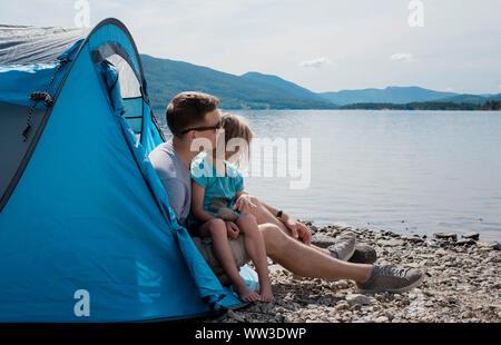 Papá abrazando a su hija mientras sentado en una tienda de acampar en el mar