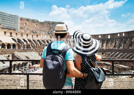Pareja de jóvenes turistas de pie dentro del Coliseo de Roma, Italia