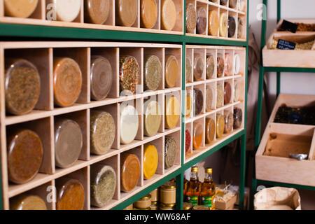 Cereales y especias que se venden en tarros de vidrio y abrir las cajas de madera en peso al eco-amigables y cero residuos shop. Pequeña tienda con self-service