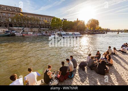 Francia, París, Sena, excursión en barco, los jóvenes en los bancos a lo largo de la Île de la Cité