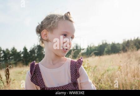 Retrato de una joven chica sonriente caminando a través de una pradera al atardecer