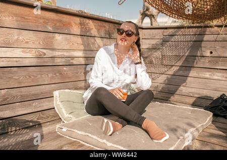 Mujer joven sentada sobre las almohadas en el dachgarten en Munich