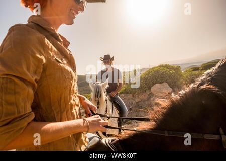 Bonito par vaqueros caucásica cabalgar en el viento ladscape pintoresco lugar. Mujer y hombre juntos divertirse con terapia de caballos y disfrutar de la puesta del sol. Las sonrisas y felicidad por concepto de independencia Foto de stock