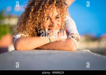 Bonita rubia hermosa joven sentar y disfrutar del sol y el clima en un día soleado de verano. Mirando y sonriendo en un tiempo de vacaciones solos libertad
