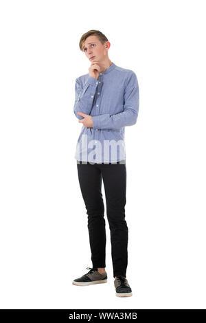 Retrato de longitud completa malestar y pensativo teen guy, mano a la barbilla, no tiene ideas para la característica en la desesperación. Los adolescentes delgados y emociones negativas